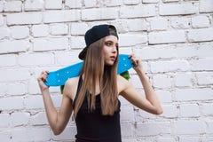 Beautiful girl in shorts poses over brick wall Stock Photos