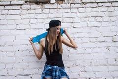 Beautiful girl in shorts poses over brick wall Royalty Free Stock Photo