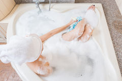 Beautiful girl showering and washing hands in bathtub. Stock Photo