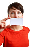 Beautiful girl showing blank business card. Sharpness on the card - face defocused Stock Images