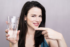 Beautiful girl showing glass of water. Portrait of a girl showing a glass of water Stock Image
