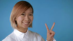 Beautiful girl showing hands gesture victory stock image