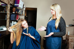 Beautiful girl showing her hair to hairdresser. Stock Photo