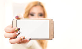 Beautiful girl showing mobile phone with empty display Stock Photo