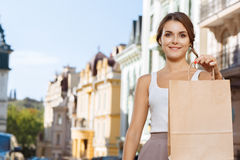Beautiful girl showing shopping bag on the street Royalty Free Stock Image
