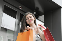 Beautiful girl showing shopping bags. Royalty Free Stock Photos