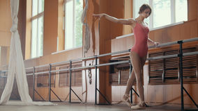 Beautiful girl shows amazing flexibility of the legs of the ballet bar