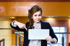 Beautiful girl shows on blank white card Stock Photography