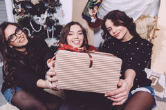 Beautiful girl shows Christmas gifts. Directly into the camera. Decorative vintage apartment Stock Photography