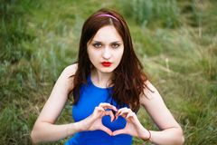 Beautiful girl shows hands the symbol of the heart and love Royalty Free Stock Photography