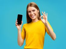 Beautiful girl shows phone and excellent sign, demonstrates that everything is fine. Photo of smiling girl in yellow sweater on blue background stock image