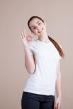 Beautiful girl shows signs of hands. And smiling Stock Image