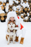 Beautiful girl with a Siberian husky in the snow. Royalty Free Stock Photos