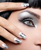 Beautiful girl with the silver makeup and nails. Beautiful girl with the silver makeup of eyes and metal nails. Fashion woman portrait. Closeup shot of female stock photography