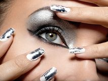 Beautiful girl with the silver makeup and nails. Beautiful girl with the silver makeup of eyes and metal nails. Fashion woman portrait. Closeup shot of female stock photo