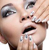 Beautiful girl with the silver makeup and nails. Beautiful girl with the silver makeup and metal nails. Fashion woman portrait royalty free stock photography