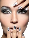 Beautiful girl with the silver makeup and nails. Beautiful girl with the silver makeup and metal nails. Fashion woman portrait stock image