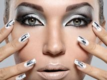 Beautiful girl with the silver makeup and nails. Beautiful girl with the silver makeup and metal nails. Fashion woman portrait stock images