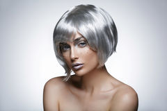 Beautiful girl in silver wig. Beautiful young woman with glowing skin, fashion make-up in short silver hair wig. Beauty shot on black background. Copy space Royalty Free Stock Image