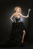 beautiful girl singer in black dress with microphone Stock Photography