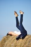 Beautiful girl sit on haystacks Royalty Free Stock Image