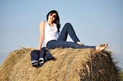 Beautiful girl sit on haystacks Royalty Free Stock Photo