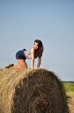 Beautiful girl sit on haystacks Stock Photo