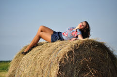 Beautiful girl sit on haystacks Stock Photos