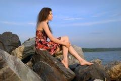 Beautiful girl sit on rock near sea Stock Photography