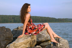 Beautiful girl sit on rock over sea Royalty Free Stock Image