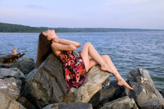 Beautiful girl sit on rock over sea Stock Image