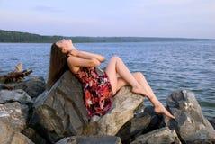 Beautiful girl sit on rock over sea Stock Image