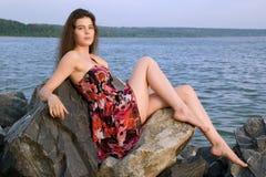 Beautiful girl sit on rock over sea. Beautiful girl sit on rock on sea coast Stock Photography