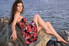 Beautiful girl sit on rock over sea. Beautiful girl sit on rock on sea coast Royalty Free Stock Photography