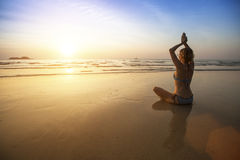 Beautiful girl sit at the seaside and meditating in yoga pose. Royalty Free Stock Images