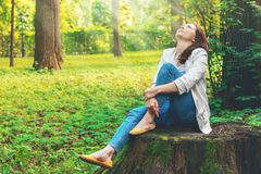 Cute woman is enjoying of picturesque nature. Camping, rest. Beautiful girl sits on a big old stump in the forest. Royalty Free Stock Photo