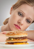 Beautiful girl sits on a diet,  sad and hamburger. Beautiful girl sits on a diet,  sad to looking at a hamburger close up Royalty Free Stock Photos