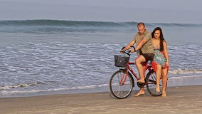 Beautiful girl sits down on bike with man against ocean stock video footage