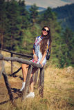 Beautiful girl sits on the fence, travels in the mountains Stock Image