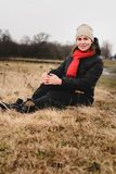 A beautiful girl sits in a field with a hat and a scarf stock photography