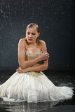 Beautiful girl sits on floor, freezes in rain Royalty Free Stock Photography