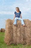 Beautiful girl sits on hay Royalty Free Stock Image