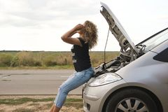 Beautiful girl sits, on the hood of a car Stock Image