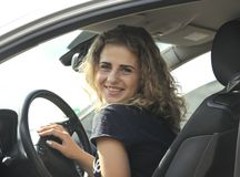 Beautiful girl sits, on the hood of a car Royalty Free Stock Photography