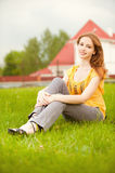 Beautiful girl sits on lawn Royalty Free Stock Images