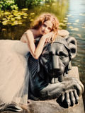 Beautiful girl sits on a lion statue. Portrait of a beautiful girl in a white dress, sitting on a lion statue in nature Stock Photos