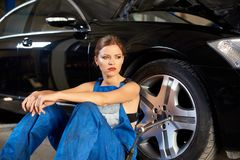 Beautiful girl sits near the black car stock image