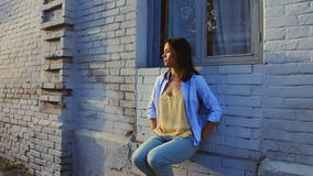 Beautiful girl sits near a brick wall. A young girl sits against a brick wall stock footage