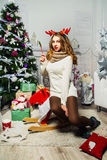 Beautiful girl sits near a Christmas tree with gifts stock image
