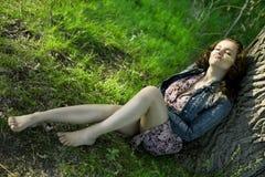 A beautiful girl sits near a tree